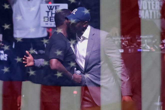 """Tallahassee Mayor and Florida gubernatorial candidate Andrew Gillum hugs Sean """"Diddy"""" Combs as the two appear together on stage at the Bring It Home Midnight Rally held at Florida A&M University's Lawson Center in Tallahassee, Fla. the night before the 2018 midterm election Monday, Nov. 5, 2018."""