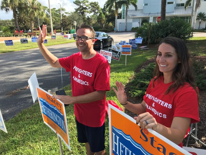 Martin County Fire Rescue staff Randy Spiegalhalter and Melissa Forte support a candidate in front of the Peter and Julie Cummings Library In Palm City during the midterm election.