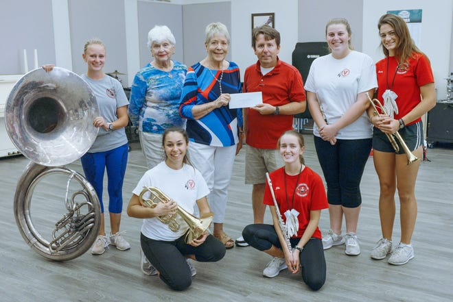 Vero Beach Friends of the Atlantic Classical Orchestra recently gave a donation to the Vero Beach High School Fighting Indians Band for its trip to London. Pictured are, from left, kneeling, Rita Cesare-De Groat and Jillie Lamothe; standing, Annika Sweetland, Vero Beach Friends board member Mary Shoaf and President Jean Beckert with Band Director Page Howell, Band Capt. Stella Rose Stawara and Gerrica Lamothe.