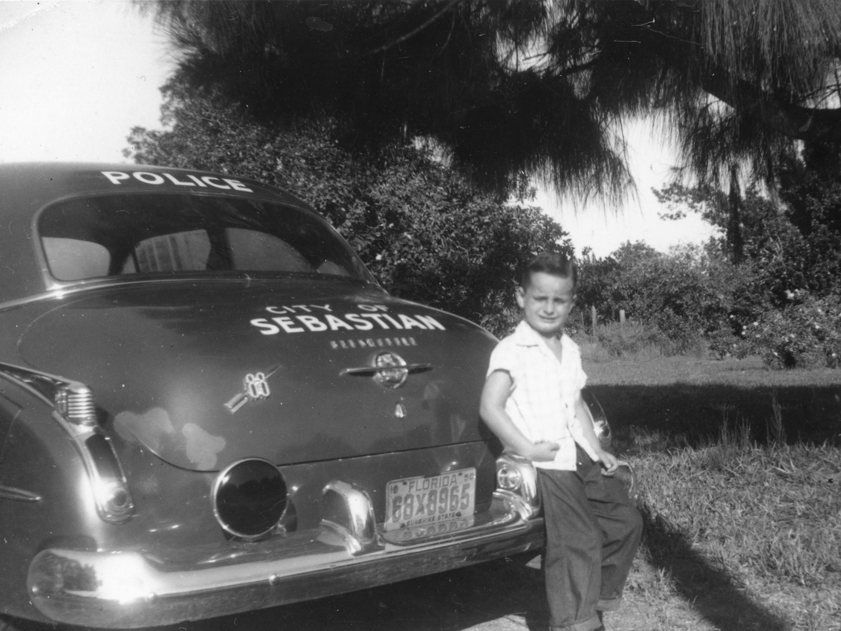 Stanley Loncon Jr. sitting on his father's patrol car in Sebastian, early 1950s. His father, Stanley Loncon Sr., was the chief of police in Sebastian at that time.