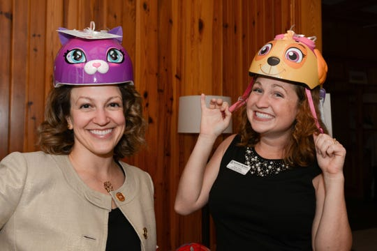 Kelly Chicvara, left, and Jenna Taylor are a hoot in their Hootie's Helmets at the Big Brothers Big Sisters' Chocolate, Champagne & Chefs fundraiser at Quail Valley River Club in Vero Beach.