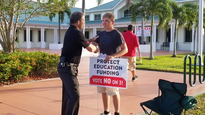 """About 20 voters waited for the doors to Tuesday morning at the Port St. Lucie Community Center, volunteers said. """"Early voting was way busier than the primaries. We expect the parking lot to stay full today,"""" said Evan Kohuth, a senior at Fort Pierce Central High. Kohuth was one of a handful of people waving signs and greeting voters outside the polling place, and the only one campaigning against Amendment 3."""