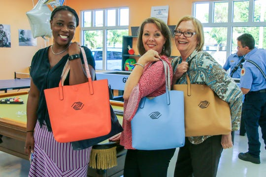 Upendo Shabazz of the Allegany Franciscan Ministries, Andrea Kochanowski of the Fort Pierce Housing Authority and Linda Hudson, Fort Pierce Mayor, show off their Boys & Girls Clubs of St. Lucie County swag during the opening of the newly remodeled Infinity Clubhouse Thursday, Oct. 25.