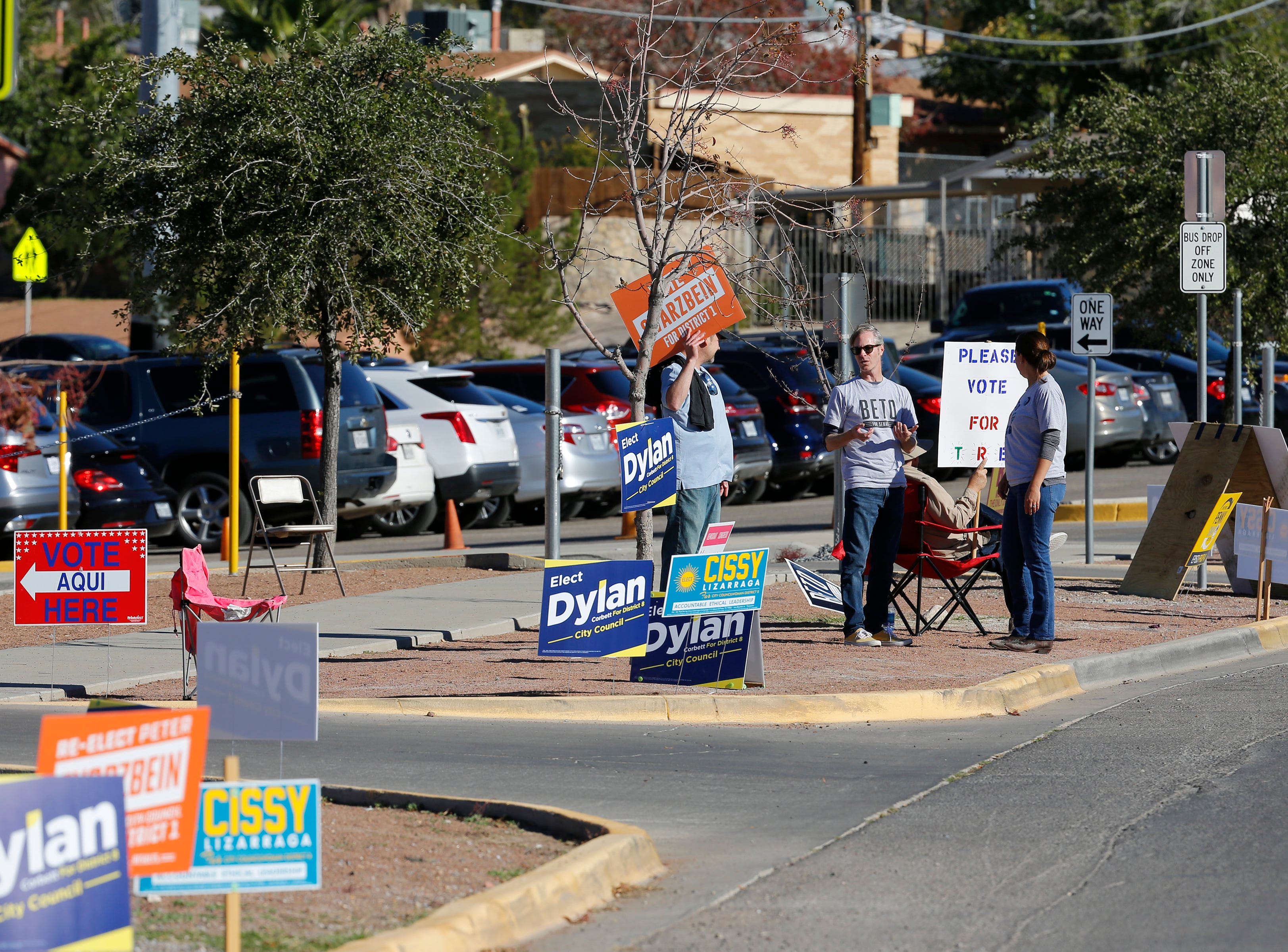 Volunteers for various candidates stand outside of Mesita Elementary School early Tuesday morning shortly after the polls opened.