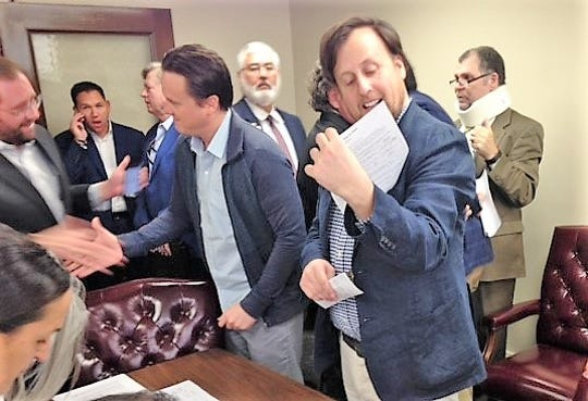 "El Paso businessman Miguel Fernandez looks at an information sheet prior to bidding in the Nov. 6 bankruptcy court auction of William ""Billy"" Abraham's properties in the old federal courthouse in Downtown El Paso. Fernandez's brother, Rodrigo Fernandez, shakes hands with bidder Matt Pepe."