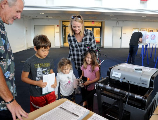 John Biggs, a polling place inspector, helps Bri Jastrow as she casts her vote Tuesday at the Ronald Reagan Presidential Library & Museum in Simi. Jastrow brought children Mason, Quinn and Berlin Jastrow with her.