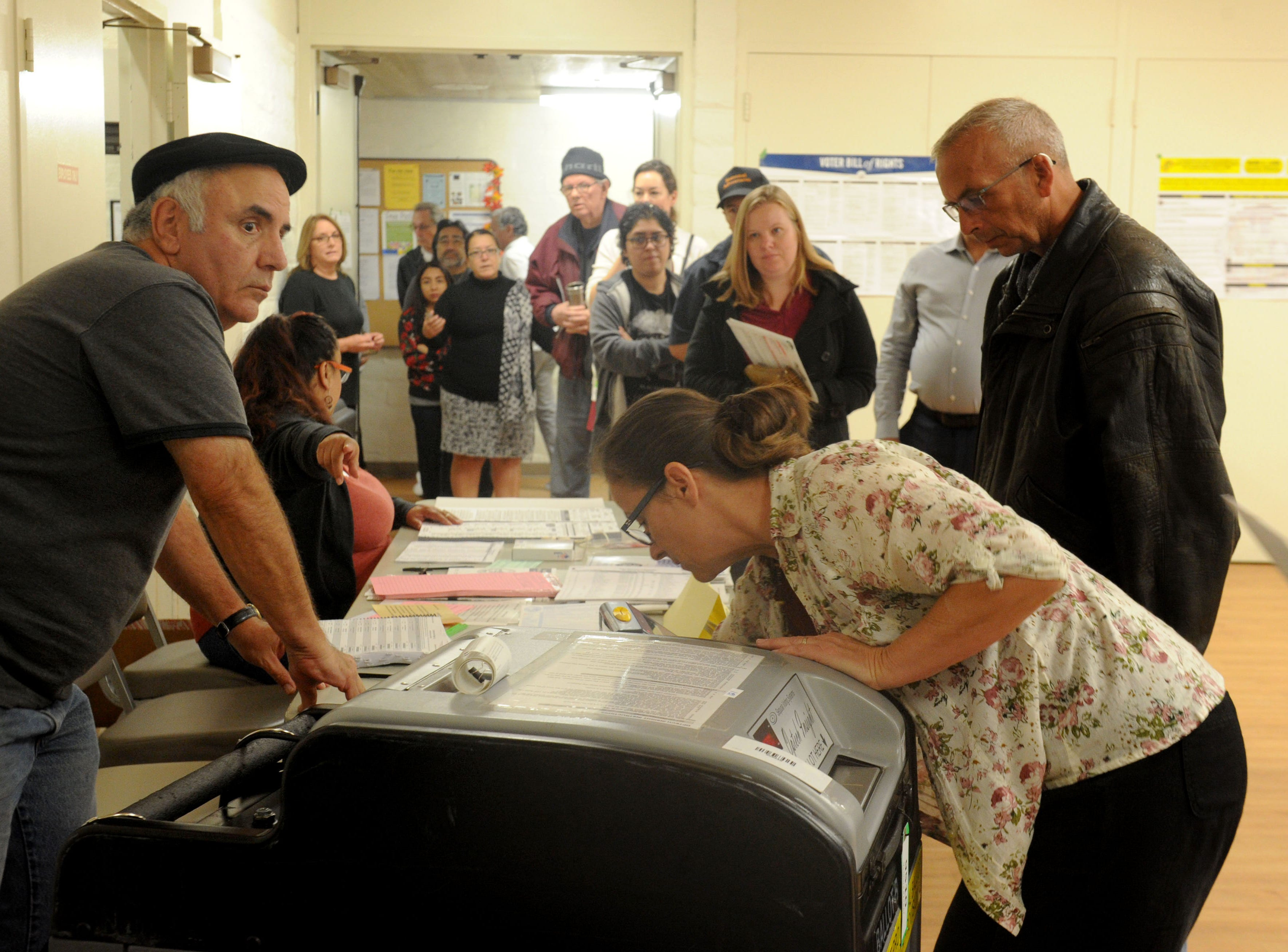 Richard Goad, left) volunteer and Sherry Cargnino (right) inspector start the voting at Ventura Avenue Adult Center. The center had a line of about 20 people.