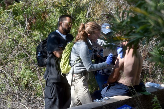 Helen Ashton and Tipu Khan, doctors at Ventura County Medical Center, administer vaccines and offer other services to a transient man in Thousand Oaks on Nov. 5 as part of an outreach program known as backpack medicine.