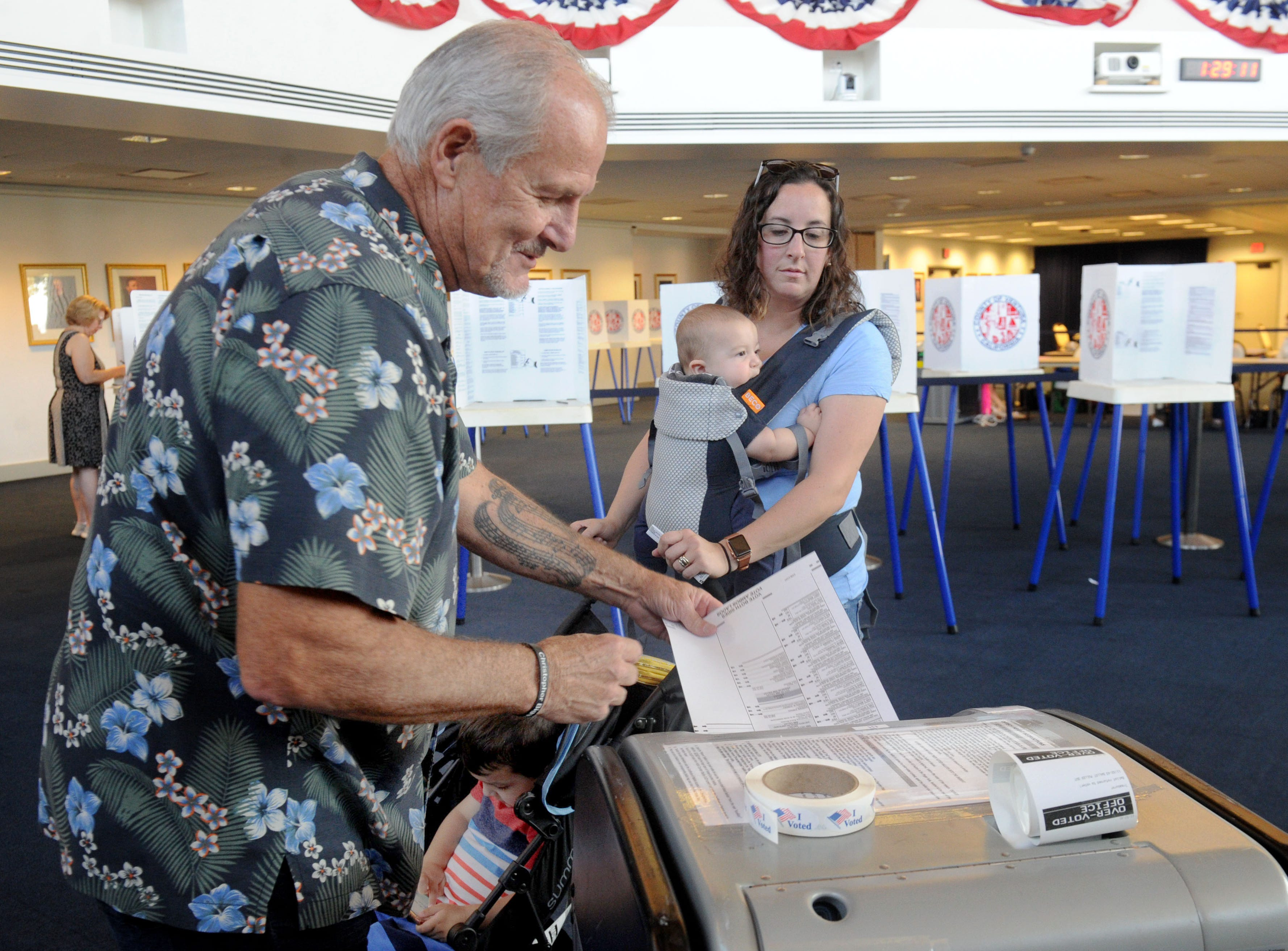 John Biggs, an inspector at the polls, helps Rochelle Mathews as she casts her vote at the Ronald Reagan Presidential Library & Museum in Simi Valley.