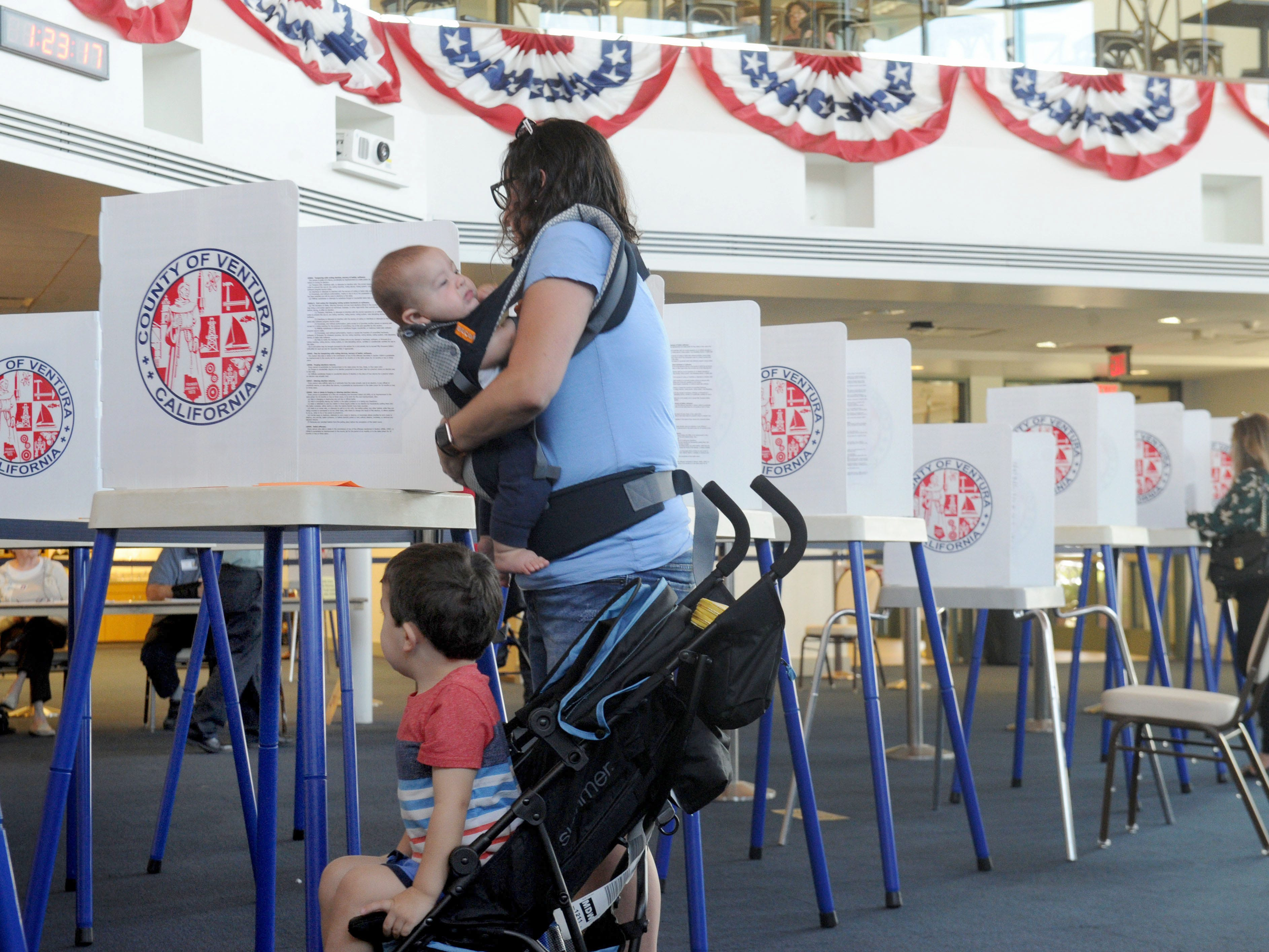 Rochelle Mathews holds her son Charlie, 3 months, as her other son, Joseph Mathews, 3, watches her vote Tuesday at the Ronald Reagan Presidential Library & Museum in Simi Valley.