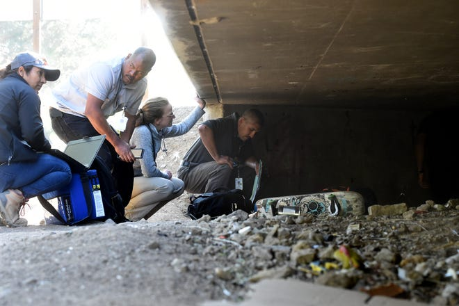 Ruben Juarez (right), Dr. Helen Ashton, James Boyd and Bianca Alvarez visit with a transient man beneath Highway 101 in Thousand Oaks on Nov. 5. The group offers vaccines, check-ups and social services as part of an outreach program by Ventura County Medical Center and other local agencies.