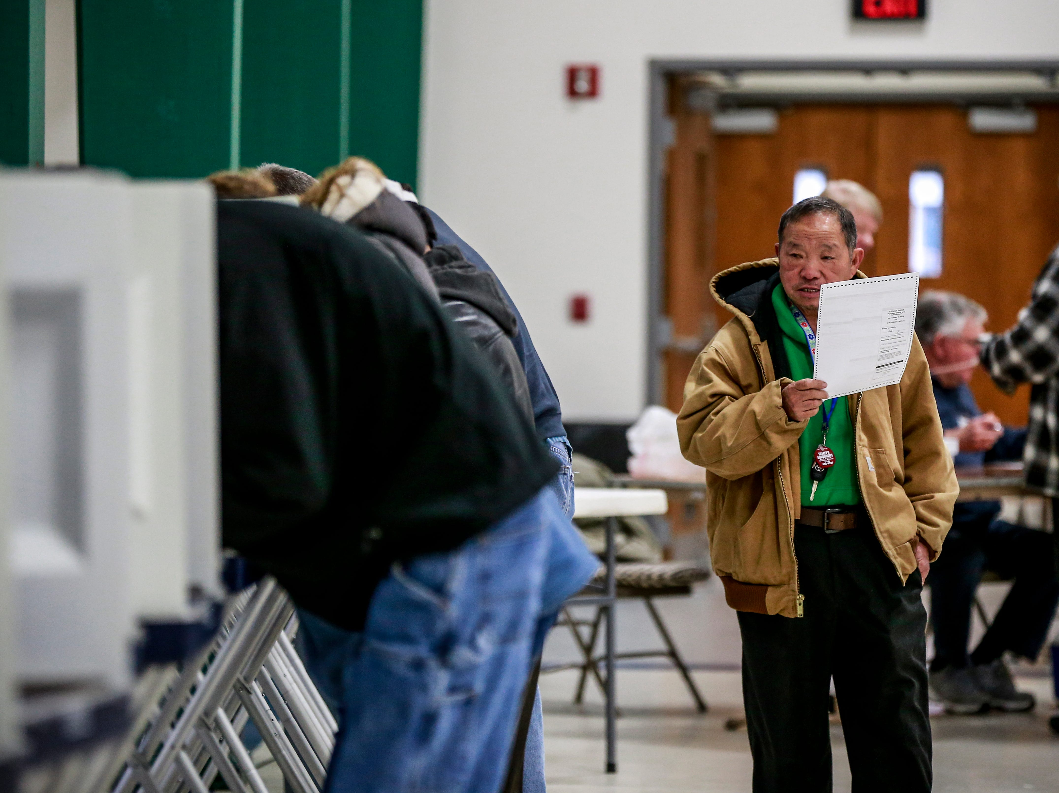 Voter Naolue Yang, right, of Wausau, approaches the ballots feeding Tuesday, Nov. 6, 2018, at the Youth Building in Marathon Park in Wausau, Wis. T'xer Zhon Kha/USA TODAY NETWORK-Wisconsin