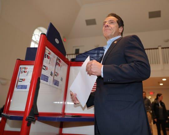 New York Governor Andrew Cuomo heads toward a privacy table as he prepares to vote at the Presbyterian Church of Mount Kisco, Nov. 6, 2018.