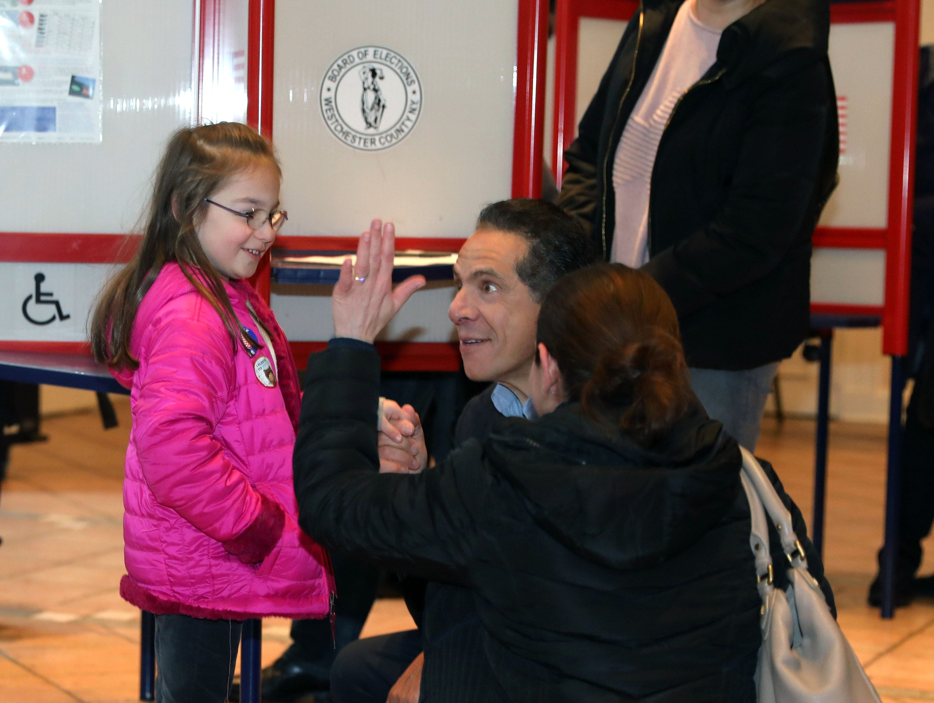 New York Governor Andrew Cuomo greets a youngster as he prepares to vote at the Presbyterian Church of Mount Kisco, Nov. 6, 2018.