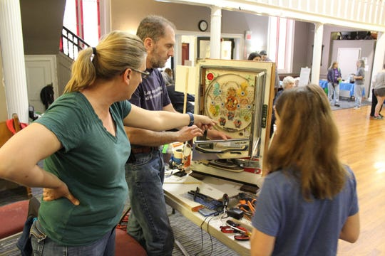 Scott Marchfield fixes a Pachinko Machine at the May Repair Cafe.