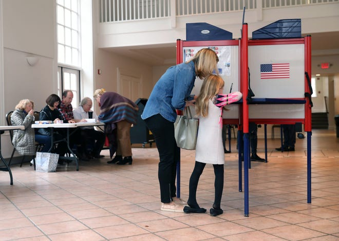 Loralee Bodo and her daughter Laina, 6,  fill in a ballot at the Presbyterian Church of Mount Kisco on Nov. 6, 2018.