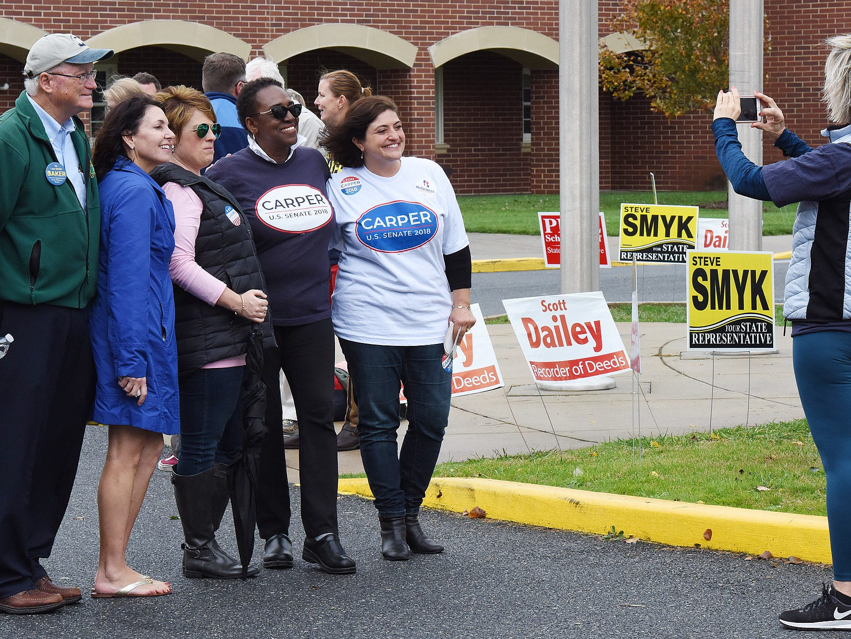 Voters have a photo taken with candidates at Cape Henlopen High School near Lewes as turnout in eastern Sussex County has been steady at polling places as candidates still seek supporters for their support.