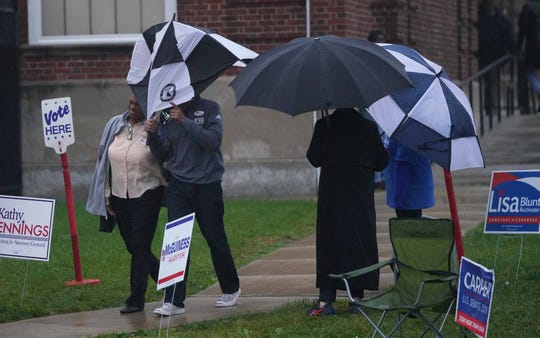 A voter fights his umbrella from the wind and rain after voting at P.S. duPont Middle School in early November.