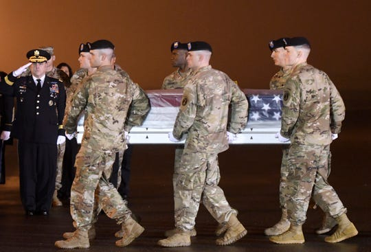 Army Chief of Staff Gen. Mark A. Milley, left, salutes as an Army carry team moves a transfer case containing the remains of Maj. Brent R. Taylor at Dover Air Force Base, Del., on Tuesday, Nov. 6, 2018. According to the Department of Defense, Taylor, 39, of Ogden, Utah, died Nov. 3, 2018, in Kabul province, Afghanistan, of wounds sustained from small arms fire. (AP Photo/Steve Ruark)