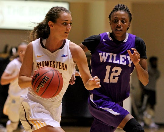 Midwestern State's Anni Scholl  dribbles by Wiley College's Grace Wellman Monday, Nov. 5, 2018, in D.L. Ligon Coliseum at MSU. The Mustangs defeated the Wildcats 91-63.