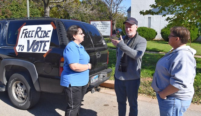 Scott Johnson talks with Diane Williams, right, and Pastor Mel Martinez of the Metropolitan Community Church Tuesday. Martinez is giving free rides for anyone wanting to go vote.
