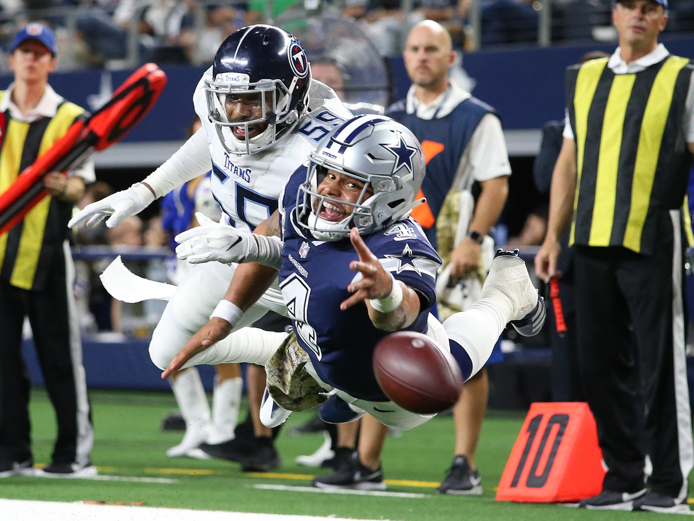 Cowboys quarterback Dak Prescott dives for a pass in the fourth quarter against Tennessee Titans linebacker Wesley Woodyard at AT&T Stadium.