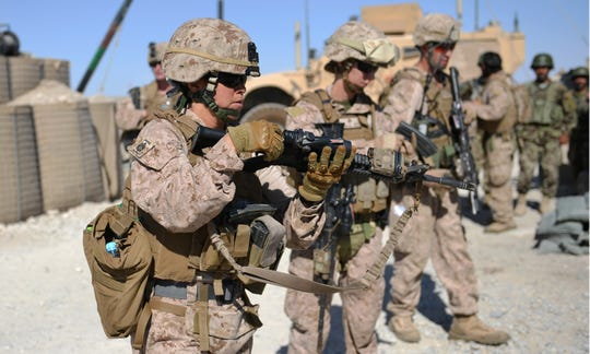 Members of Female Engagement Team (FET), US Marines GySgt Michelle Hill (L) and Cpl. Reagan Odhner (C) from the 1st battalion 7th Marines Regiment unload their M4 rifles after a patrol with Afghanistan National Army (ANA) soldiers in Sangin in Helmand Province on June 6, 2012.