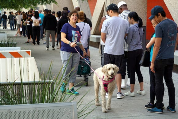 Tammy Versing and her dog Ben Ben provide water to voters at an early voting polling station Sunday at West Los Angeles College in Culver City, California.