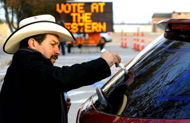 """Jose Vargas, 56, draws """"vote"""" and """"vota"""" on his Mazda SUV windows on Nov. 6, 2018, in Dodge City, Kan., while waiting to give rides to the polls to midterm election voters who needed transportation or accidentally showed up at the wrong polling place."""