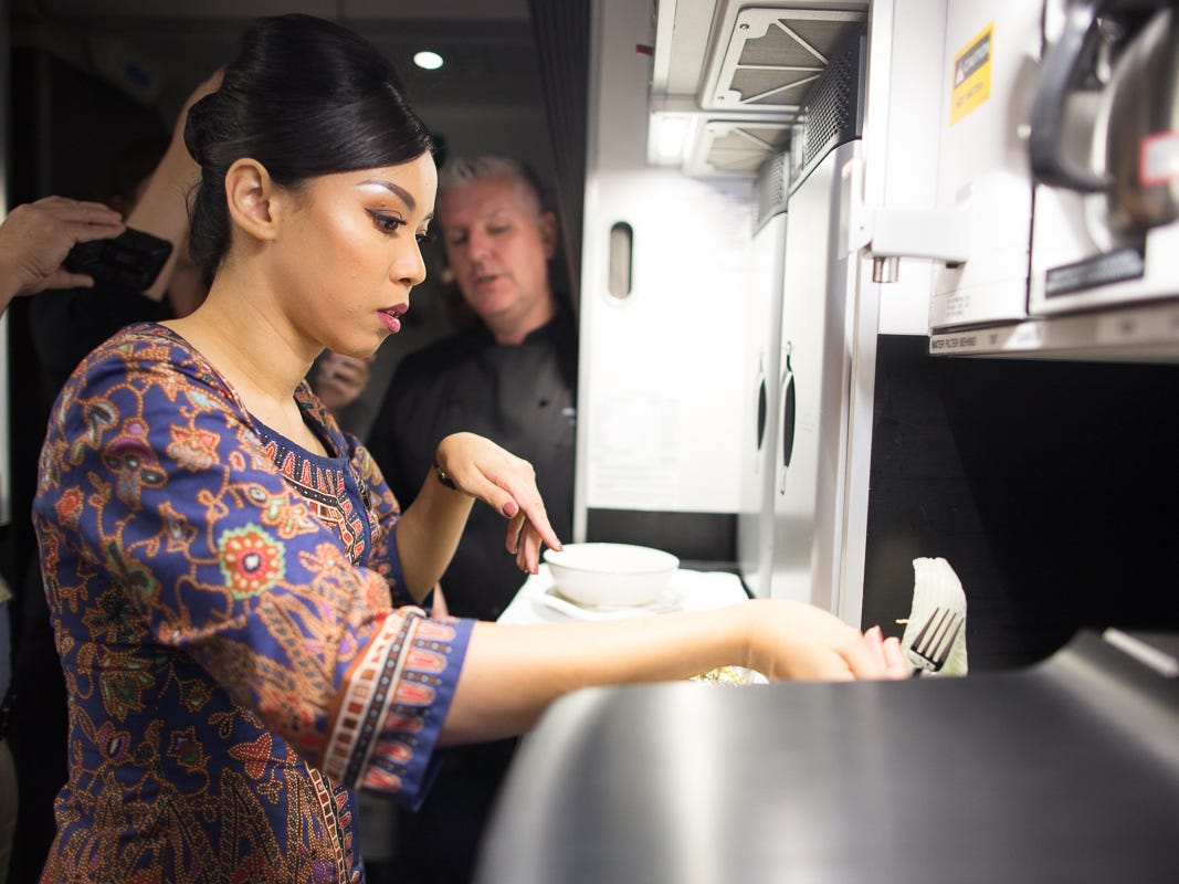 A flight attendant prepares a meal on the world's longest flight, Singapore Airlines Flight 21, between Newark and Singapore on Oct. 12, 2018.