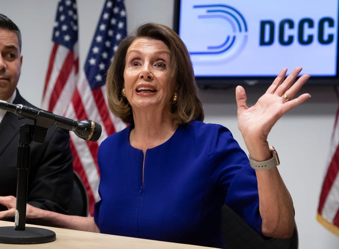 House Democratic Leader Nancy Pelosi of California, center, and Democratic Congressional Campaign Committee Chairman Rep. Ben Ray Lujan, D-N.M., left, speak with reporters on Election Day at the Democratic National Committee headquarters in Washington, Nov. 6, 2018.