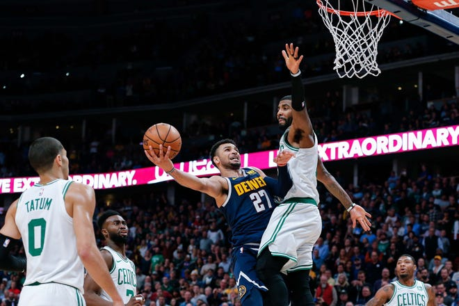 Boston Celtics guard Kyrie Irving (11) defends against Denver Nuggets guard Jamal Murray (27) in the fourth quarter at Pepsi Center.