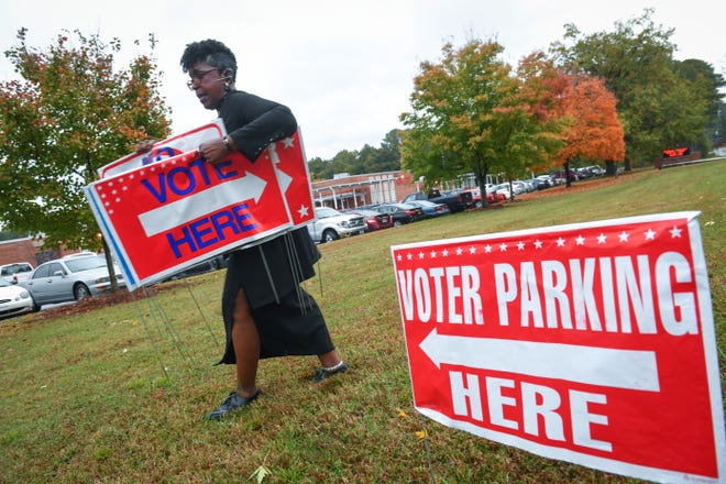 Hollis Bass Knight, the assistant manager of a poll district in Clayton County, places precinct signs outside of Anderson Elementary School in Conley, Ga., as polls open Nov. 6, 2018.