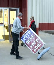 A poll worker wheels out a sign as the voting begins in Dodge City, Kansas, during the Nov. 6, 2018 midterm election.