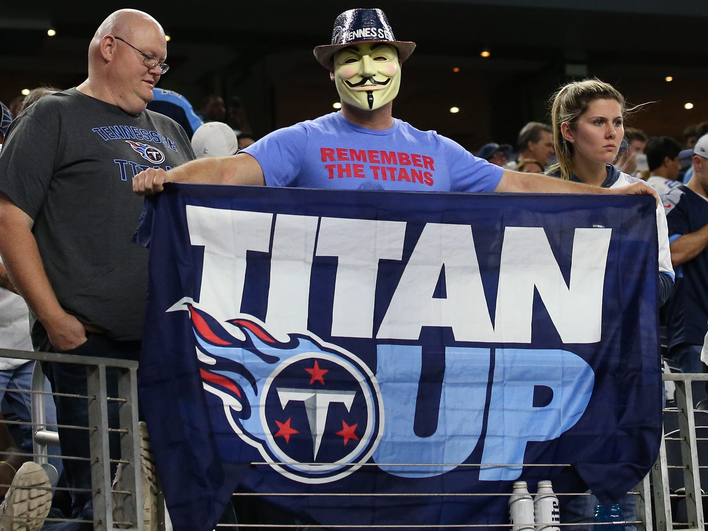"""A Tennessee Titans fan holds up a """"Titan Up"""" flag during the game against the Dallas Cowboys at AT&T Stadium."""