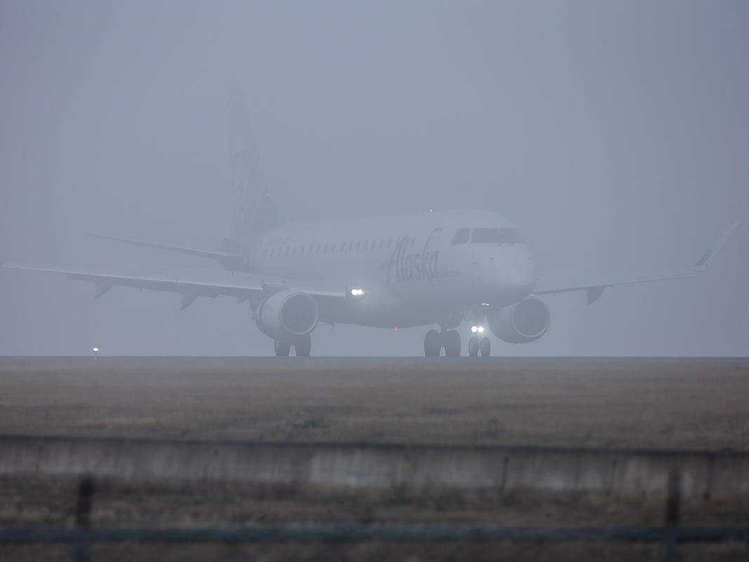 Shrouded in heavy fog, an Alaska Airlines-branded Embraer E170 rolls out after landing at Seattle-Tacoma International Airport in October 2018.