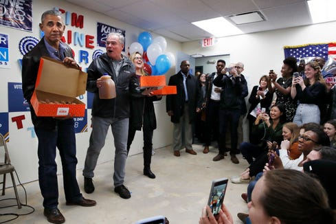 Former President Barack Obama, left, holds open a box of doughnuts with Sen. Tim Kaine, D-Va., holding apple cider, and Virginia state Sen. Jennifer Wexton, who is running for Congress, as Obama surprised Democratic volunteers in Fairfax Station, Virginia, on Monday, Nov. 5, 2018.