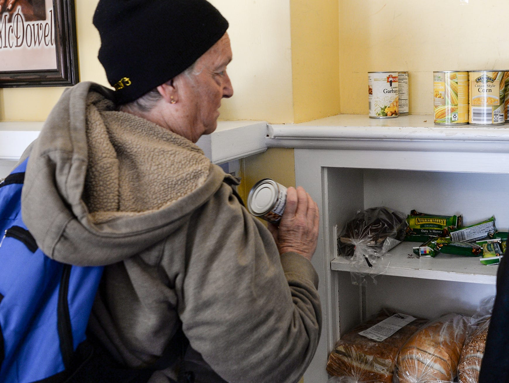 Sarah Nicholson, 65, of Anderson picks a can of food during her visit to the Anderson Soup Kitchen in November.