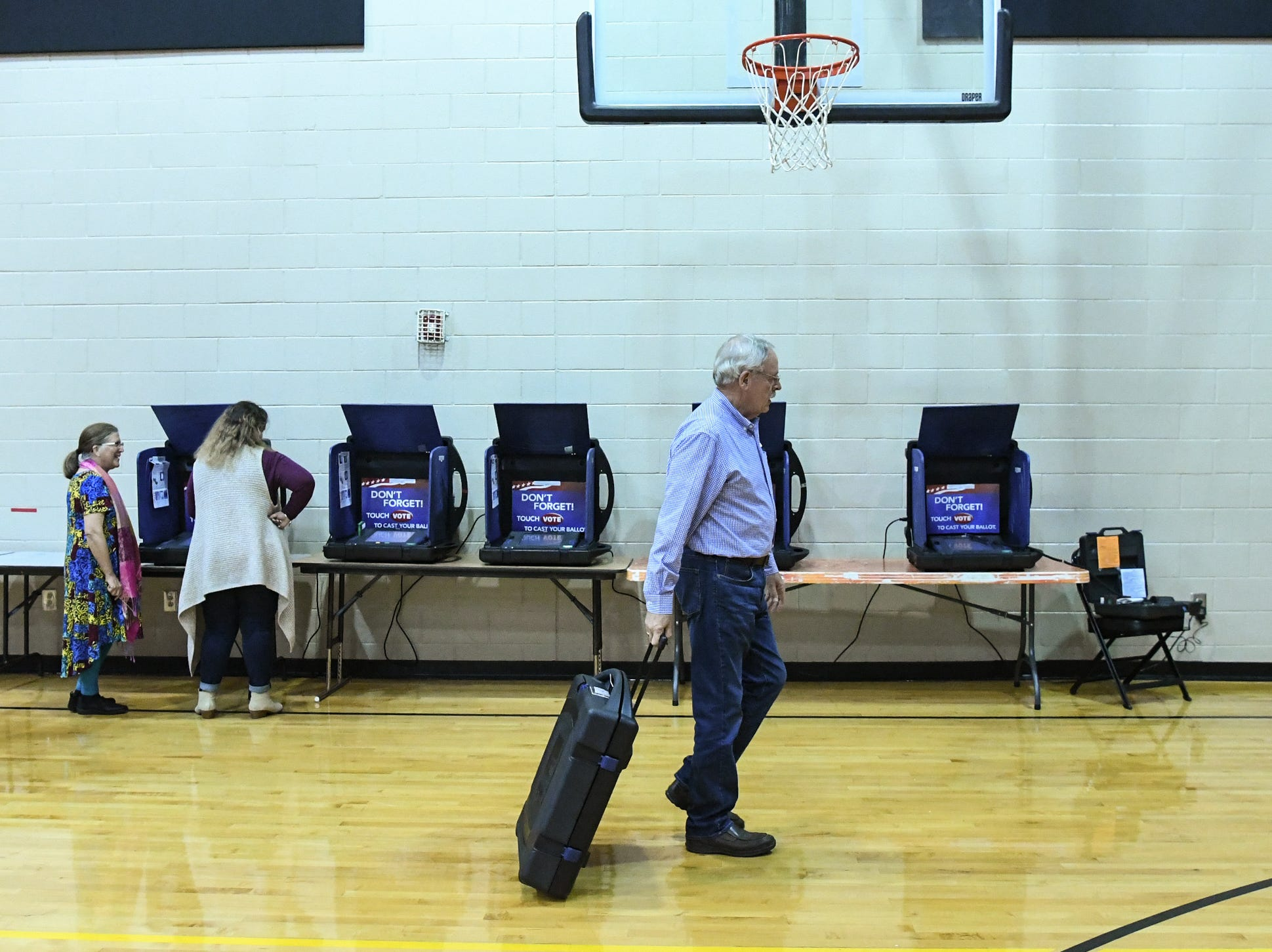 Ray Calhoun, a poll manager at Hopewell precinct at T.L. Hanna High School, rolls one of the voting booths to return to storage, after totals on a memory card were removed after 7 p.m., in Anderson on Tuesday, November 6, 2018.
