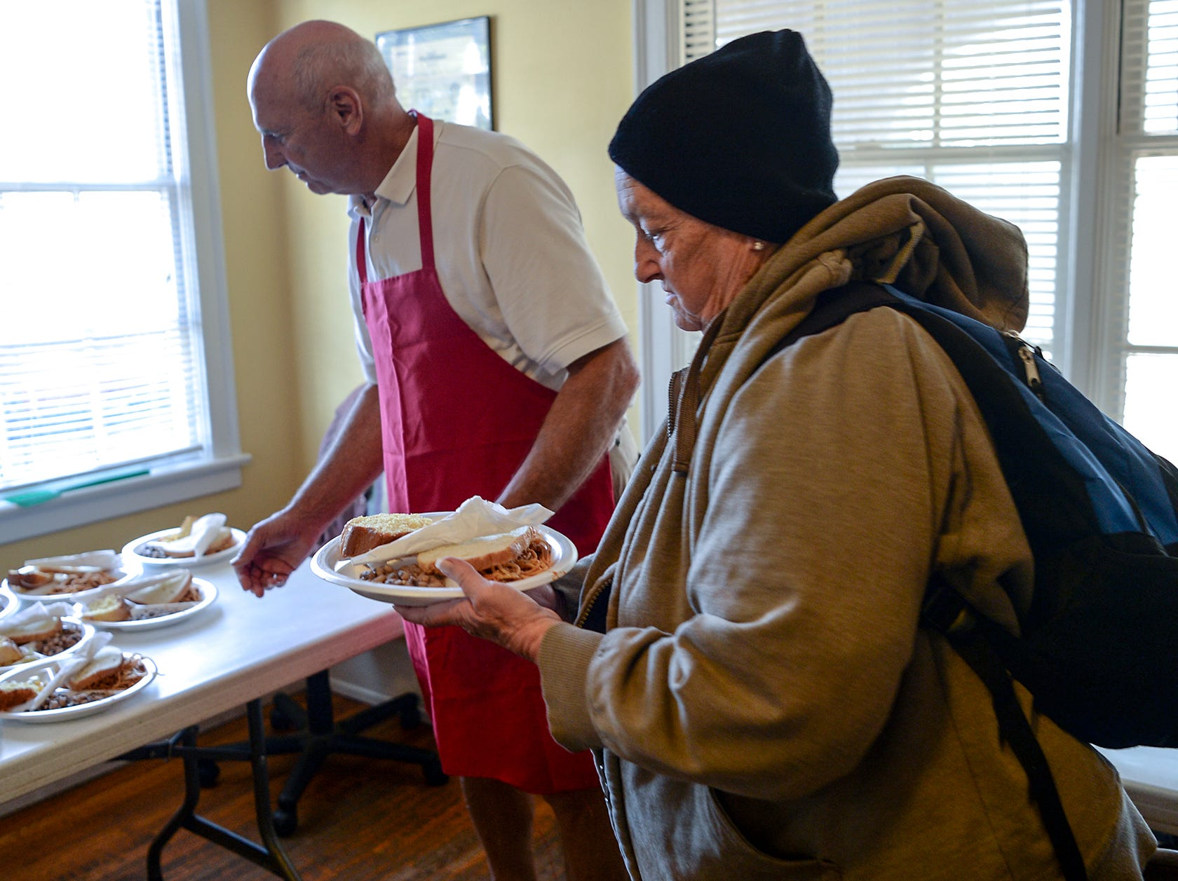 Sarah Nicholson, 65, of Anderson gets a plate of food from volunteer Rick Brosche of Anderson during her visit to the Anderson Soup Kitchen in November.