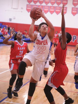 Cooper's Jennika Willis (32) drives to the basket against a Wichita Falls Hirschi defender. Hirschi won the game 51-37 on Tuesday, Nov. 6, 2018, at Cougar Gym.