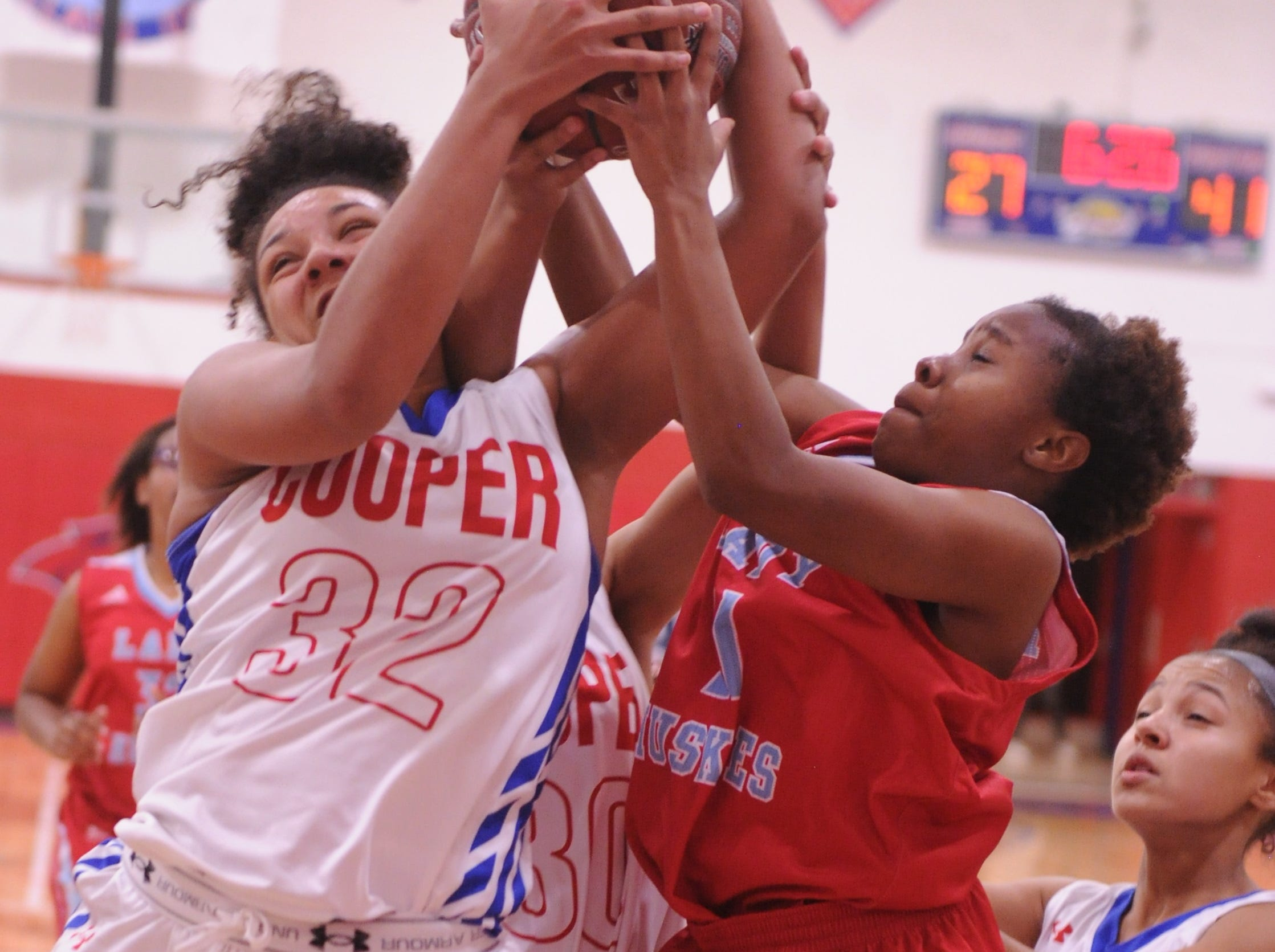 Cooper's Jennika Willis (32) battles a Wichita Falls Hirschi player for a rebound as Aziah Joe (13) looks on. Hirschi won the game 51-37 in the season opener for both teams Tuesday, Nov. 6, 2018, at Cougar Gym.