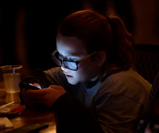 Raina Holamon, 13, checks election results and social media while attending the Democrats election watch party Tuesday at The Mill with her mother Leah and sister Salem.