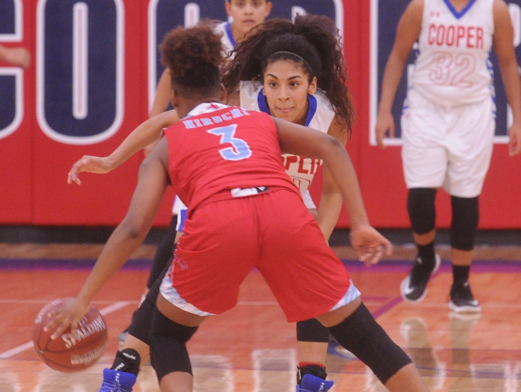 Cooper's Keiana Kemp defends against Wichita Falls Hirschi's Eternity Hull (3). Hirschi won the game 51-37 in the season opener for both teams Tuesday, Nov. 6, 2018, at Cougar Gym.