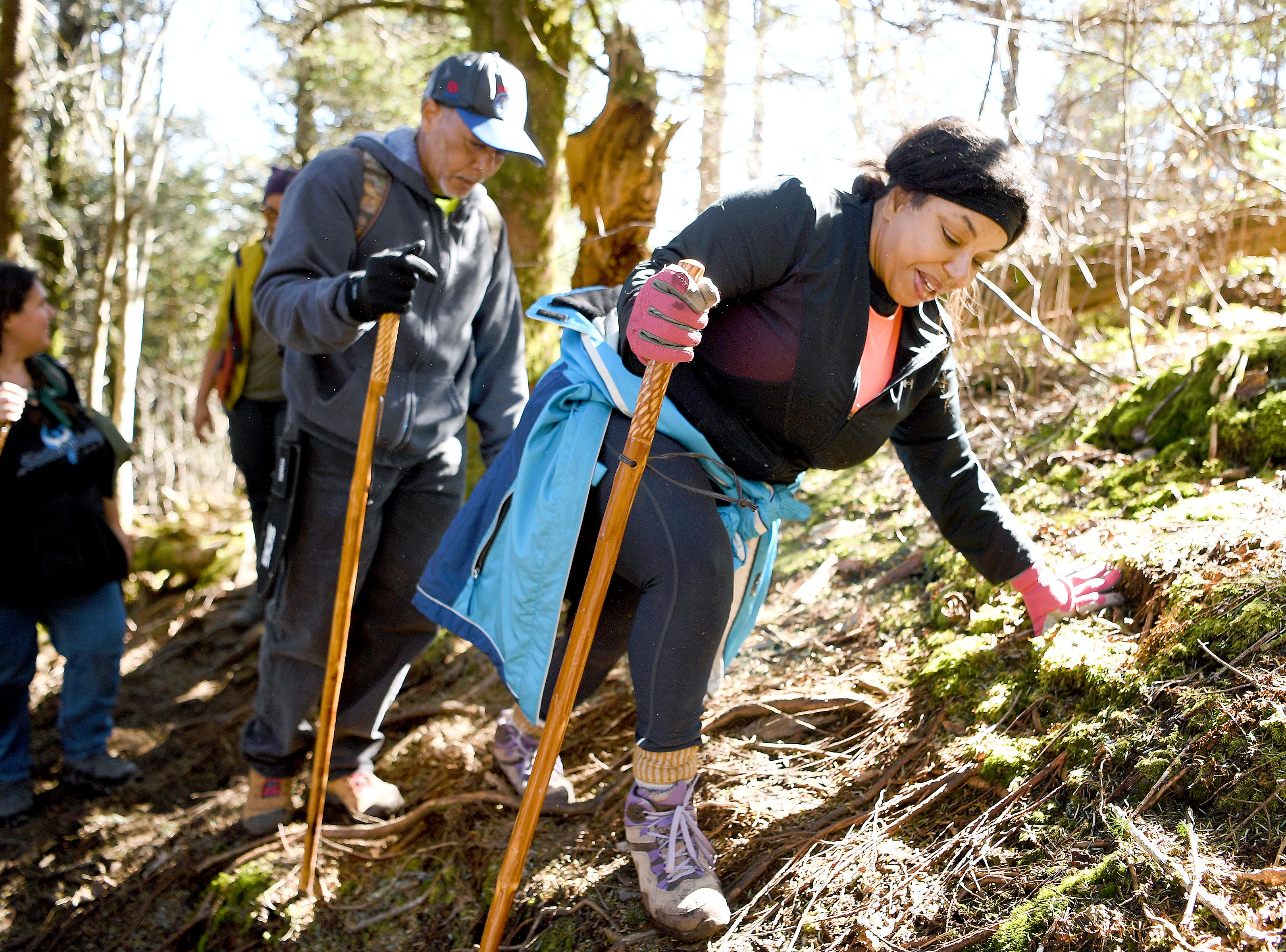 Tanya Cummings scrambles along the unofficial Plott Balsam Trail as she hikes with Pathways to Parks on Oct. 30, 2018. Pathways to Parks is an outdoors group that aims to get more people of color outside and into our National Parks.