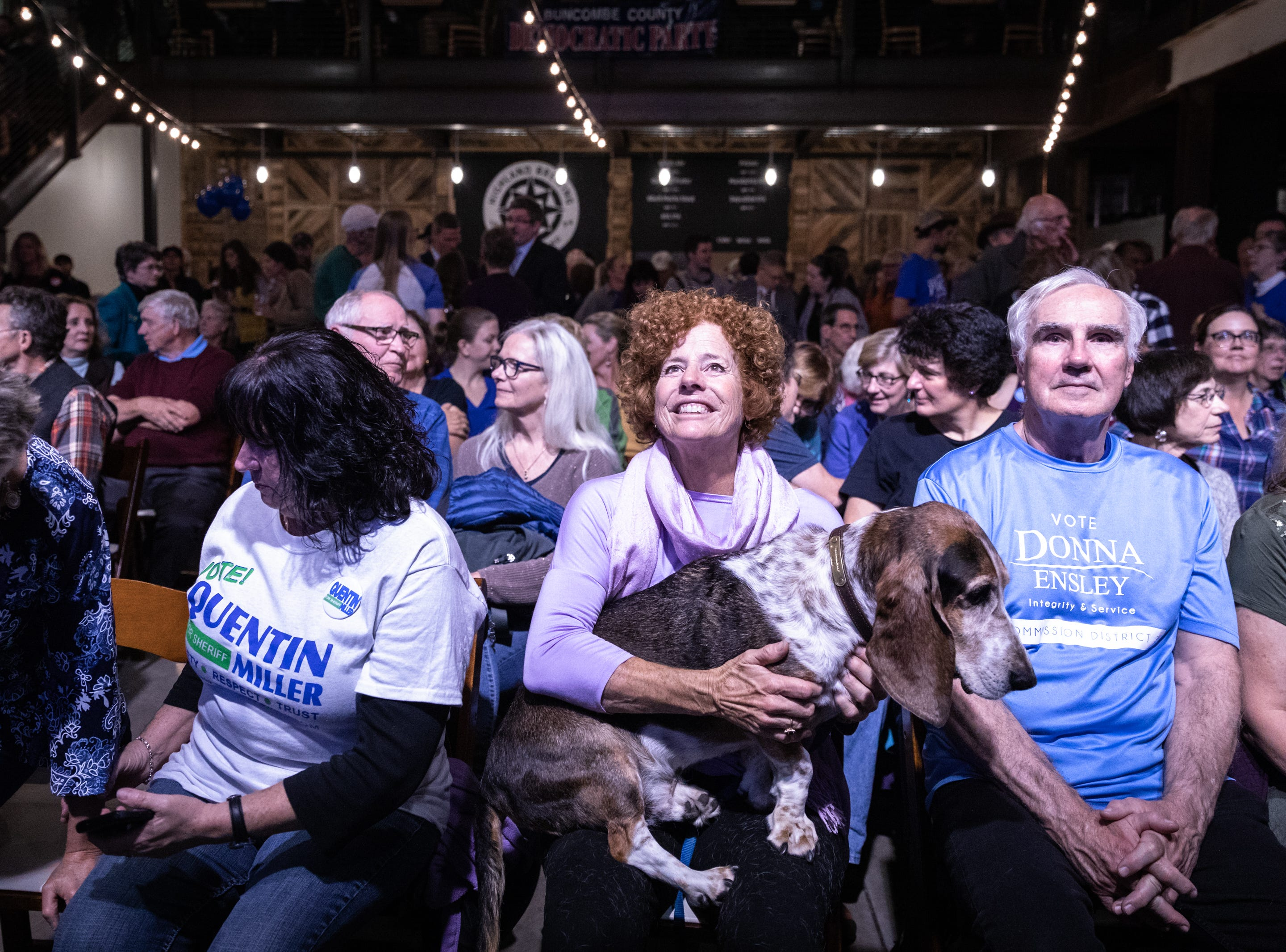 "Harriett Nettles, of Weaverville, watches as midterm elections come in with her ""Democratic"" Bassett hound Milo at the Buncombe County Democratic Party's election night party at Highland Brewing Nov. 6, 2018."