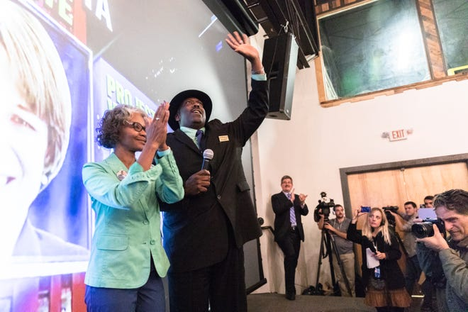 Quentin Miller, newly elected Buncombe County sheriff, waves to supporters with his wife Karen Sconiers, at the Democratic Party election night party at Highland Brewing Nov. 6, 2018.