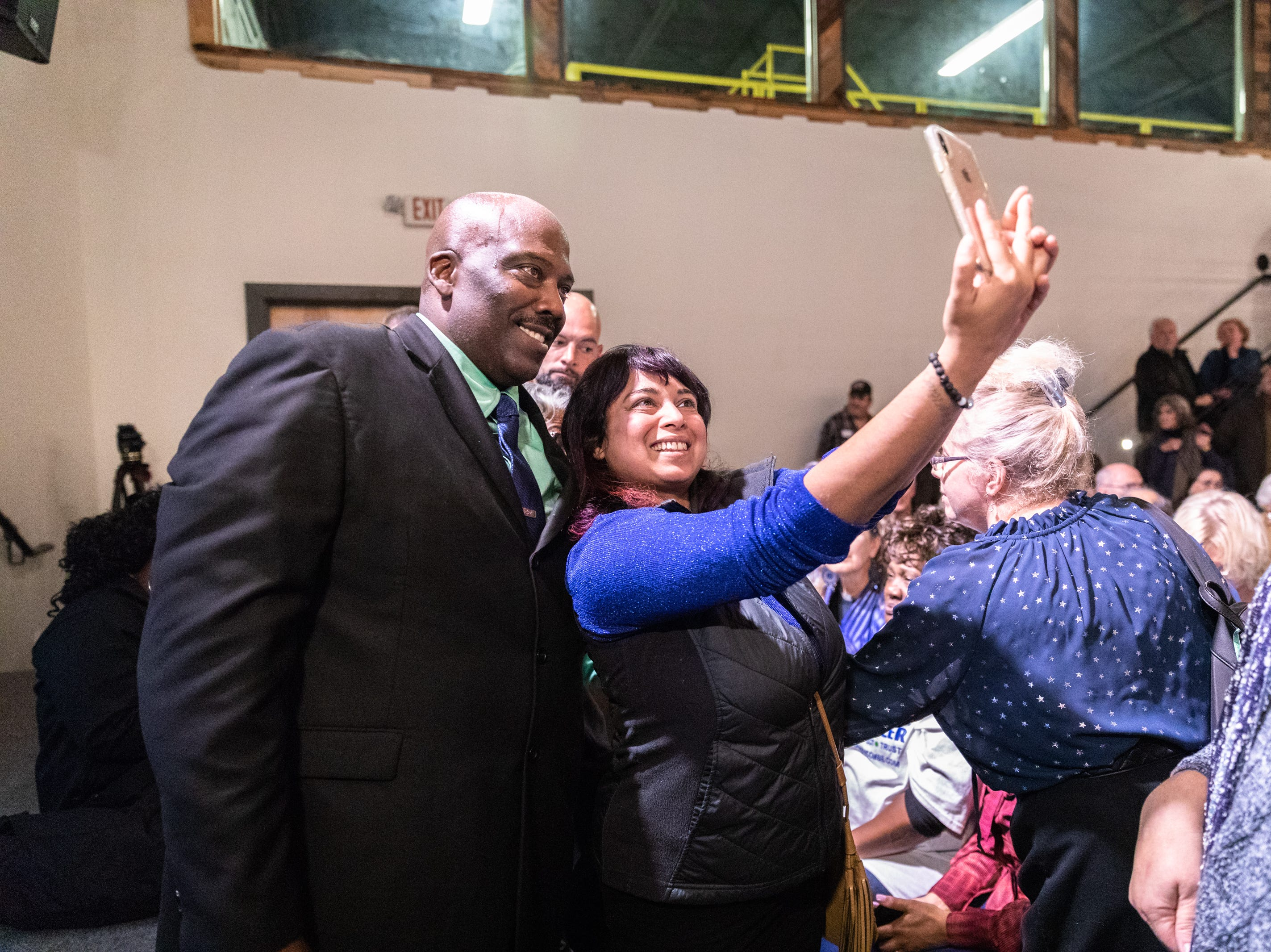 Quentin Miller, newly elected Buncombe County sheriff, poses for a cell phone photo with Pramela Thiagesan, of Asheville, at the Democratic Party election night party at Highland Brewing Nov. 6, 2018.