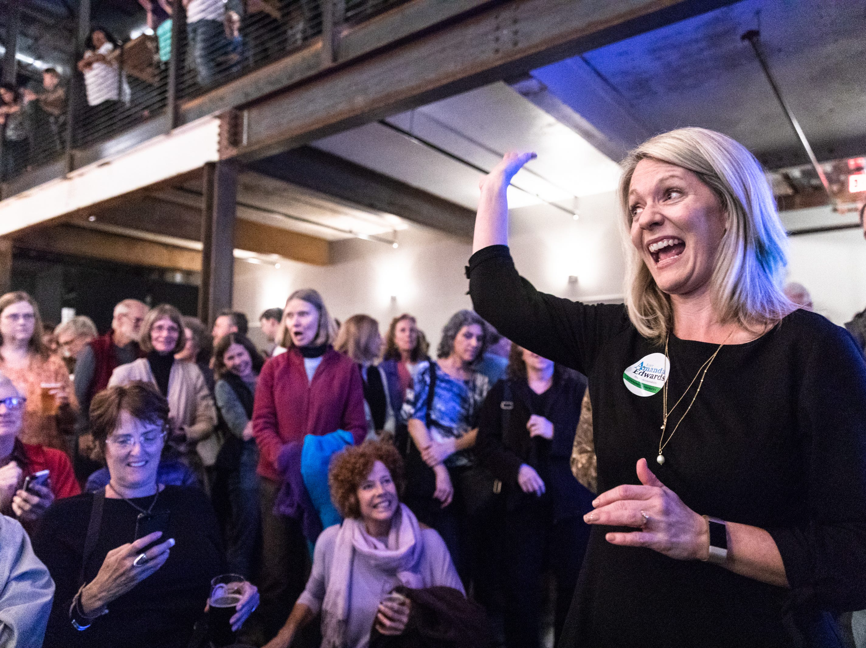 Amanda Edwards waves to supporters at the Buncombe County Democratic Party's election night party at Highland Brewing after winning her seat as the county commissioner for district 2, Nov. 6, 2018.