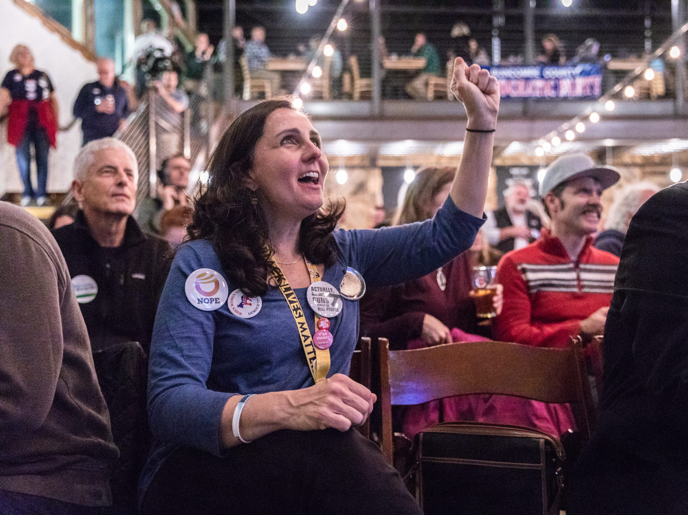 Julie Lehman, of Asheville, cheers as she watches favorable results come in at the Buncombe County Democratic Party's election night party at Highland Brewing Nov. 6, 2018.